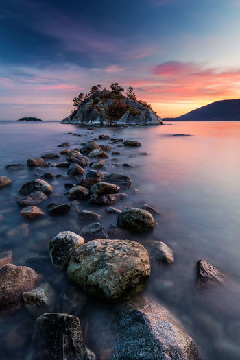 Rock hopping at high tide during sunset at whytecliff park, west vancouver , canada.