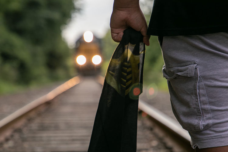 Midsection of person holding fabric while standing on railroad track
