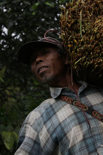 Low angle portrait of farmer carrying crop on shoulder