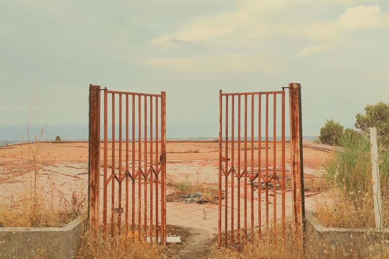 Wooden gate on beach against sky