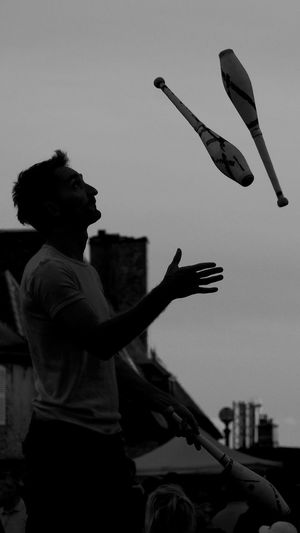 Low angle view of man playing flying in city against sky