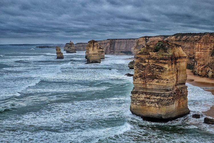 Idyllic shot of twelve apostles sea rocks in sea against cloudy sky