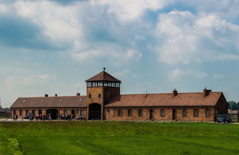 Main entrance to nazi concentration camp of Auschwitz II Birkenau in Oświęcim, Poland. Beautiful view of the gate during a sunny spring day. Auschwitz  HUMANITY Jewish Morning Panoramic Poland Tourists Architecture Building Building Exterior Concentration Day Education Grass History Holocaust Land Museum Nazism People Prisoners Sky Travel Travel Destinations Visit