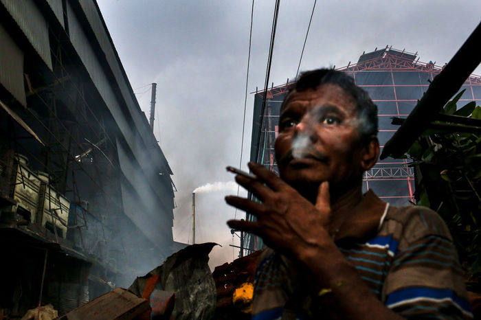 A steel worker takes a break to smoke a cigarette beside the steel mills. With an estimated market size of 300 Billion BDT, the steel industry in Bangladesh is currently experiencing an upsurge in demand. This growth is driven mostly by government spending on infrastructure projects, which accounts for 40% of steel consumption in Bangladesh. Air Pollution Bangladesh Carbon Dioxide Close-up Cloud Day Environmental Pollution Industrial Pollution Lifestyles Low Angle View Mammal Portrait Sky Smoke Smoking Steel Mill