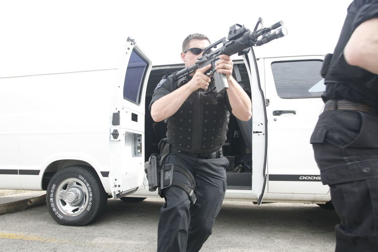SWAT team member leaves a van. Accidents And Disasters Ar15 Day Gun Men Occupation Outdoors People Police Protection Protective Workwear Real People S.W.A.T. Standing Swat Uniform Weapon