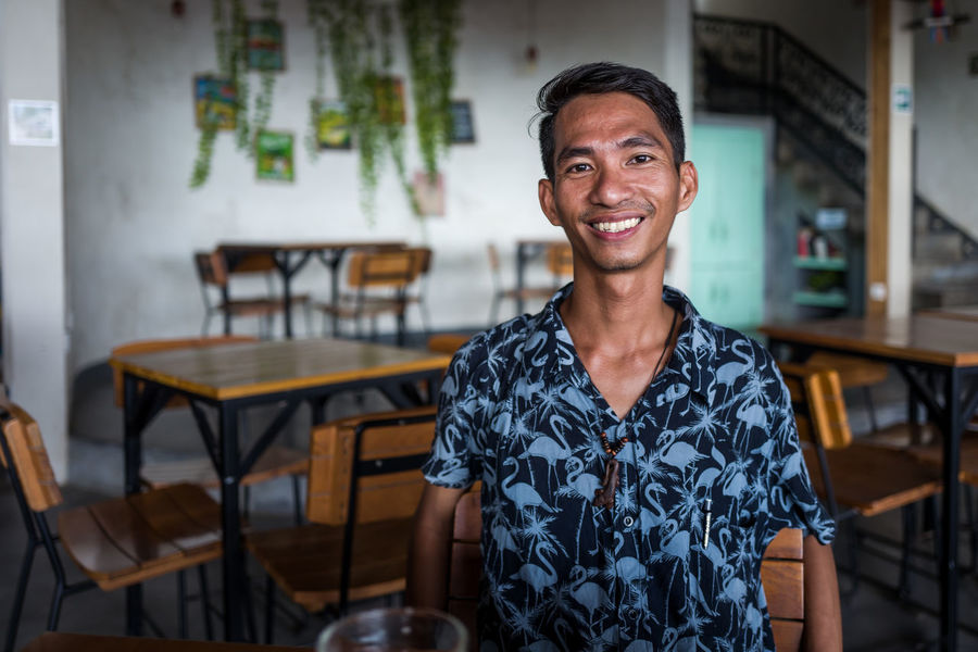 Labuan Bajo guy Business Cafe Casual Clothing Chair Coffee Shop Emotion Front View Hairstyle Happiness Indoors  Looking At Camera One Person Portrait Real People Restaurant Seat Sitting Smiling Table Waist Up Young Adult