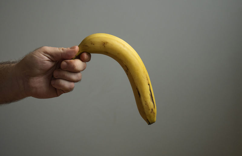 Cropped image of person holding banana against white background