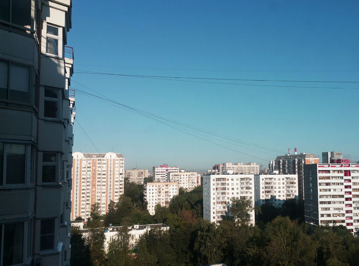 Low angle view of apartment buildings against clear blue sky
