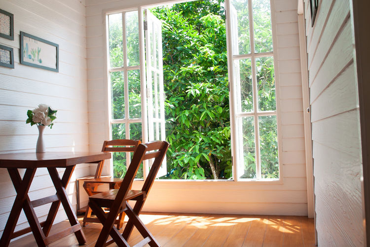 Living room with big window garden view, country style with wooden furniture Window Indoors  Seat Chair No People Home Interior Table Day Domestic Room Glass - Material Architecture Nature Furniture Wood - Material Flower Pot Living Room Bay Window Country Home House White