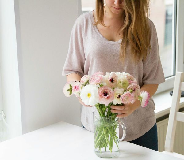 Midsection of woman placing flower vase on table at home