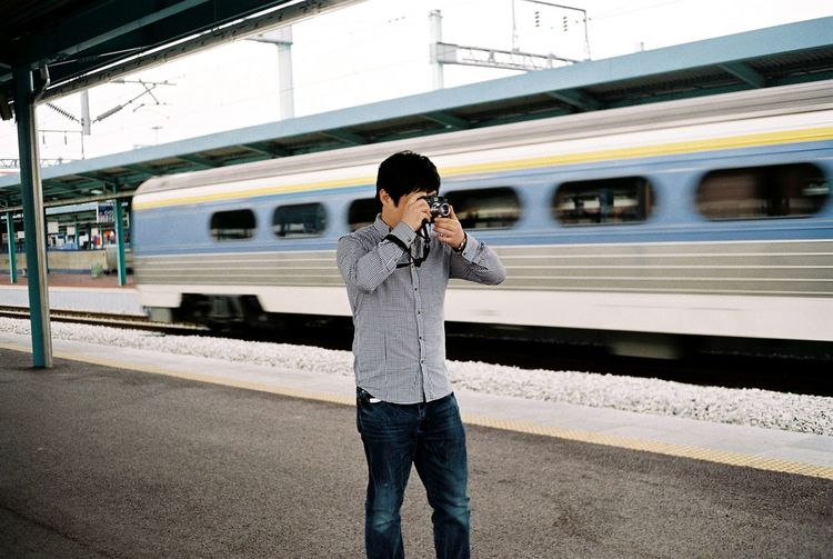 Man Photographing At Railroad Station Platform