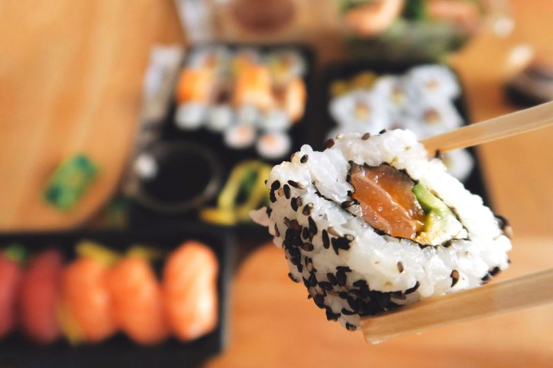 Close-Up Of Chopsticks Holding Sushi Roll Over Table