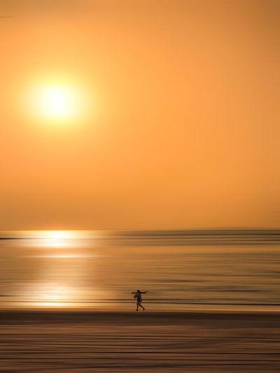 Silhouette man on sea against orange sky during sunset