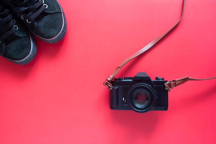 Directly above shot of black camera and shoes over pink background
