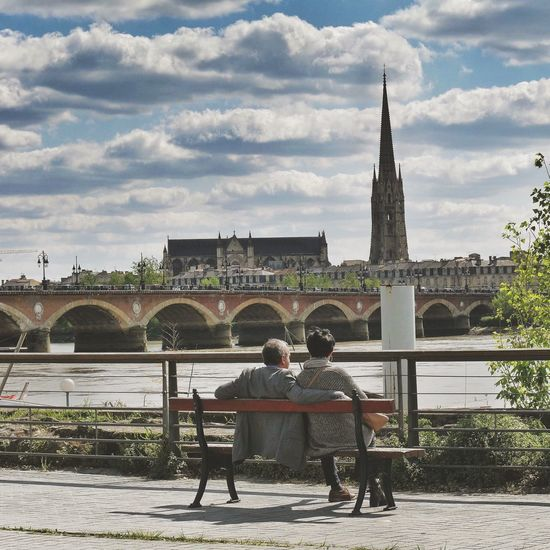 Rear view of man and woman sitting on bench against river in city
