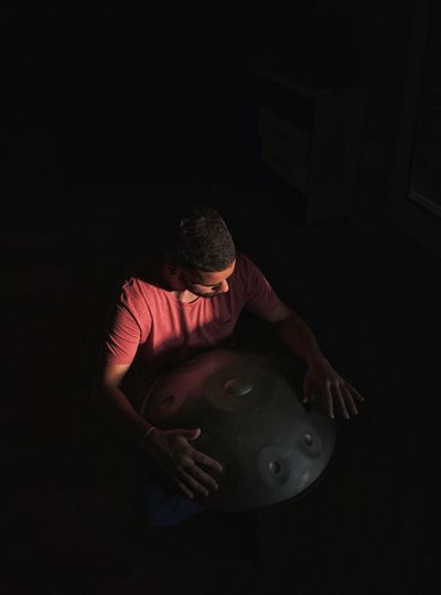 Indoors  One Person Real People Black Background Playing Day People hands Hanging Out Hangdrum Drum