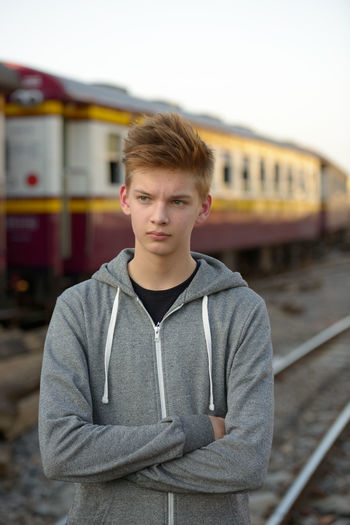 Portrait of young man standing by train