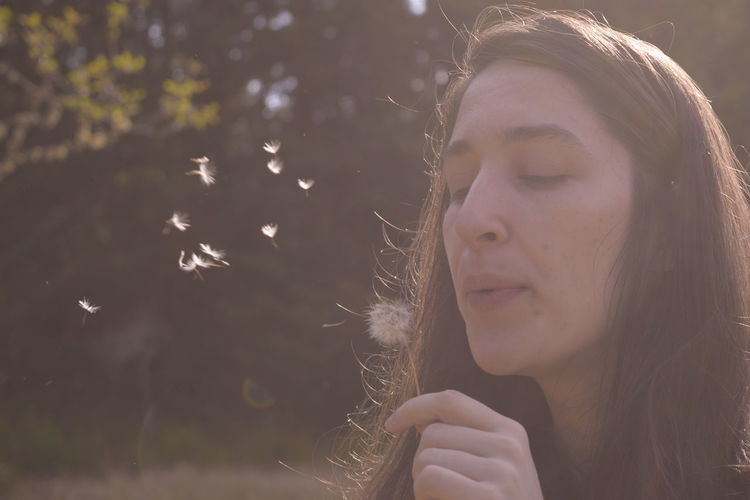Close-up of beautiful woman blowing dandelion seed