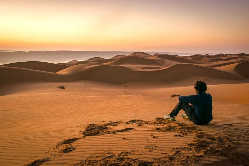 Sunrise Land One Person Men Sunset Sky Leisure Activity Beauty In Nature Climate Rear View Landscape Adult Tranquility Nature Sand Lifestyles Real People Desert Arid Climate Orange Color Scenics - Nature