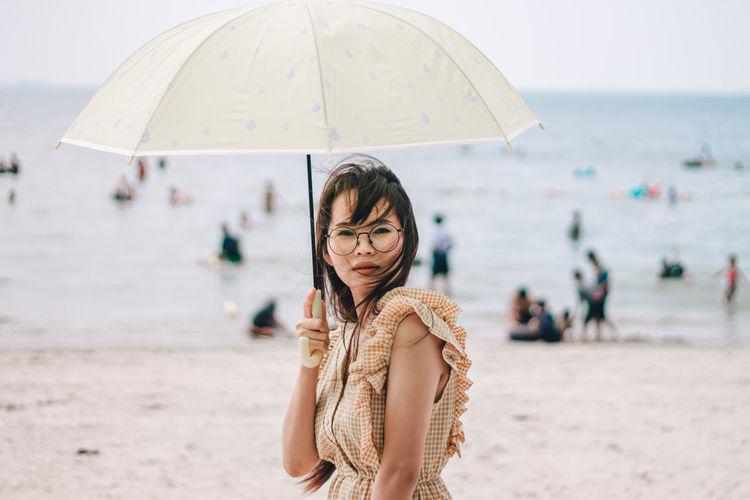 Portrait of beautiful woman wearing sunglasses holding umbrella standing at beach