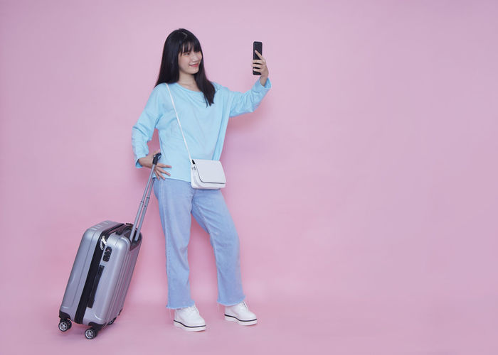 Full length of woman using phone while standing against pink background