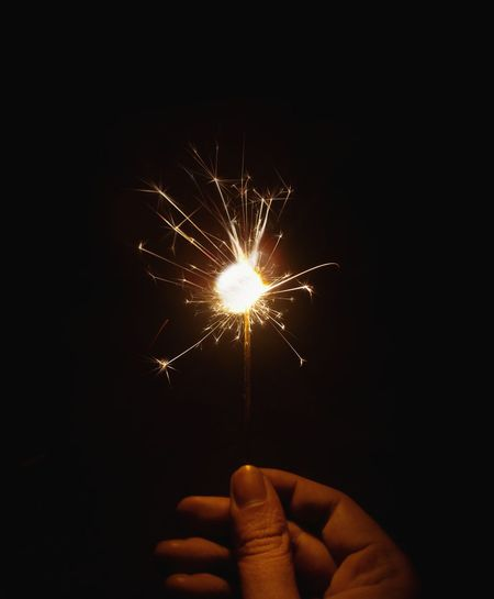 Person hand holding firework display at night