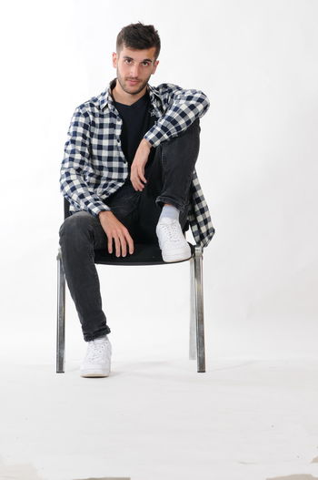 Full length portrait of young man sitting on chair over white background