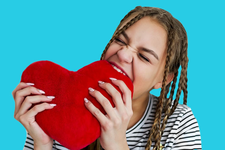 Teen girl bites red plush heart. Emotional girl with pigtails and eyes closed. Isolate on turquoise background Red Studio Shot Colored Background Love Emotion Headshot Front View Positive Emotion One Person Indoors  Portrait Heart Shape Women Holding Eyes Closed  Young Women Young Adult Leisure Activity Blue Background Hairstyle Nail Valentine's Day - Holiday Innocence Beautiful Woman