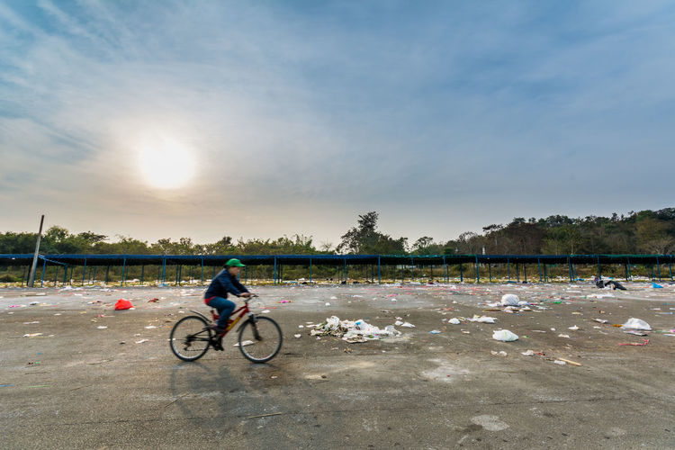 Man cycling by garbage at parking lot