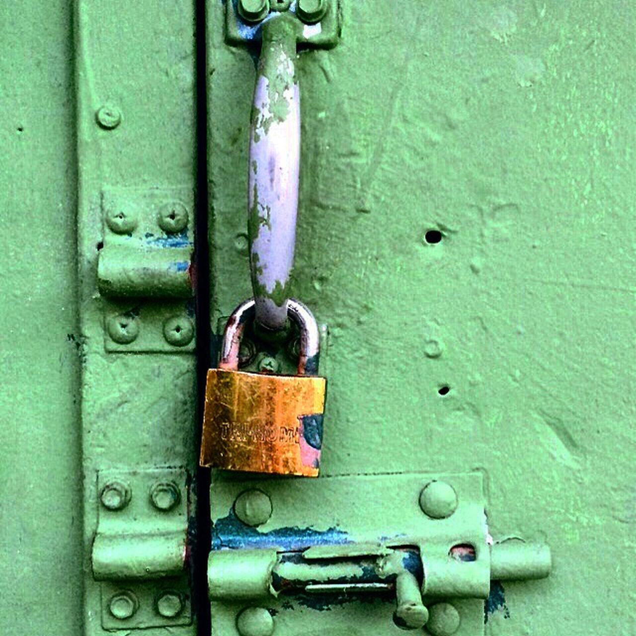 CLOSE-UP OF PADLOCKS ON RUSTY DOOR