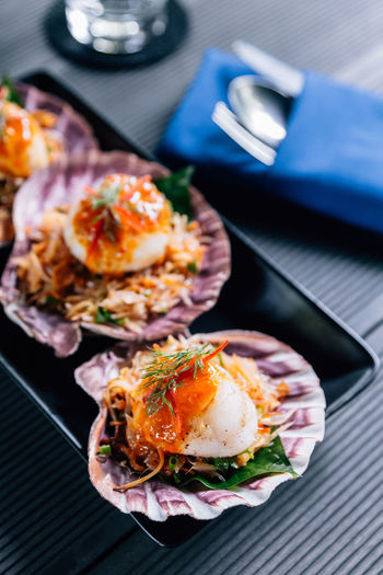 Grilled scallop in shell with spicy pomelo salad served in black plate. Food And Drink Food Seafood Freshness Healthy Eating Ready-to-eat Wellbeing Japanese Food Sushi Plate Indoors  Rice Close-up No People Asian Food High Angle View Still Life Fish Egg Meal Place Mat