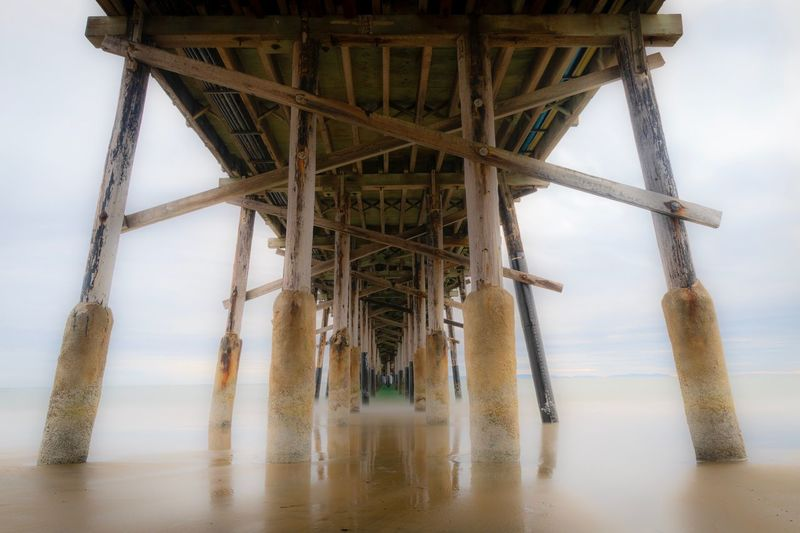 Under Pier Serene Calm Long Exposure Pier EyeEm Selects Built Structure Sky Architecture Water Nature Low Angle View No People Architectural Column Beach Underneath Day