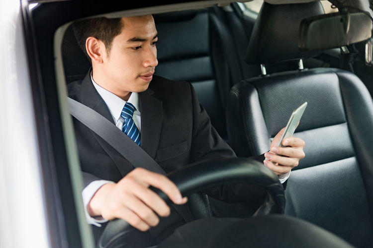Businessman Using Mobile Phone While Sitting In Car