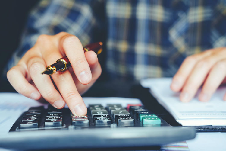 Midsection of businessman calculating at desk