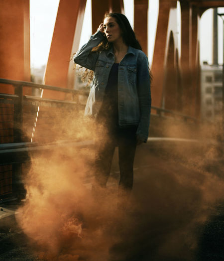 Adult Beautiful Woman Casual Clothing Clothing Emotion Hairstyle Lifestyles Looking Motion One Person Real People Smoke - Physical Structure Standing Women Young Adult