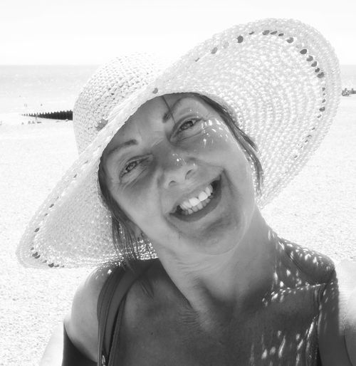 Portrait of cheerful woman wearing hat while standing at beach