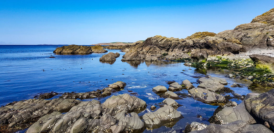 Rock formations on shore against clear blue sky