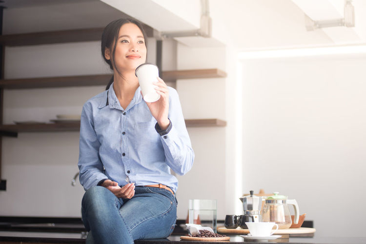 Woman having drink while sitting at home
