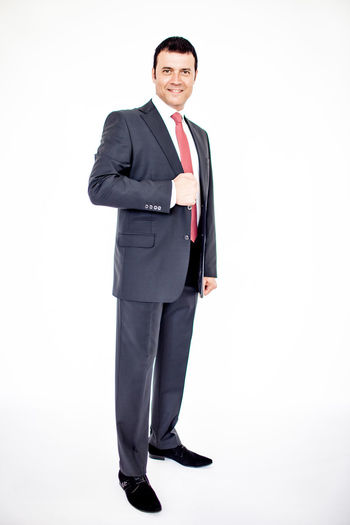 Man in classic suit on the white background. Studio shot. Adult Business Business Person Businessman Ceo Confidence  Formalwear Full Length Happiness Looking At Camera Males  Manager Men Menswear Necktie One Person Portrait Positive Emotion Smiling Standing Studio Shot Suit Well-dressed White Background Young Adult