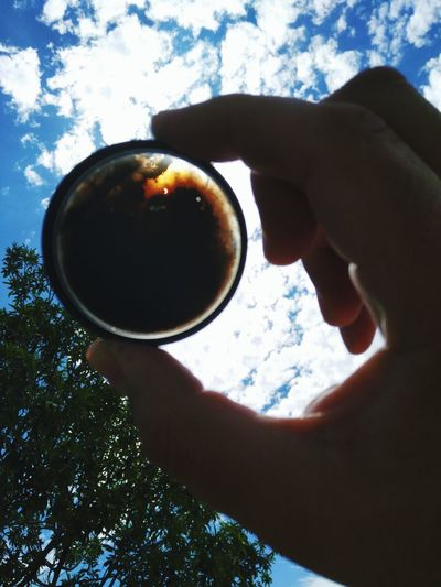 Close-up of woman hand holding coffee cup against sky