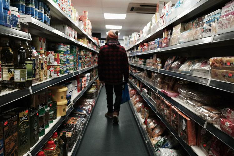 Rear view of man walking in supermarket
