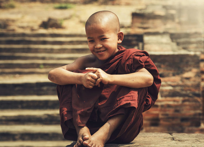 Smiling Monk Sitting On Retaining Wall Against Steps Outside Temple