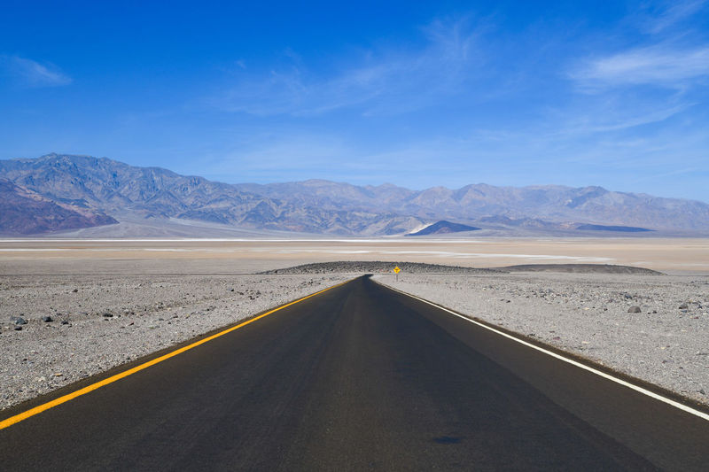 Scenic view of empty road by desert against sky