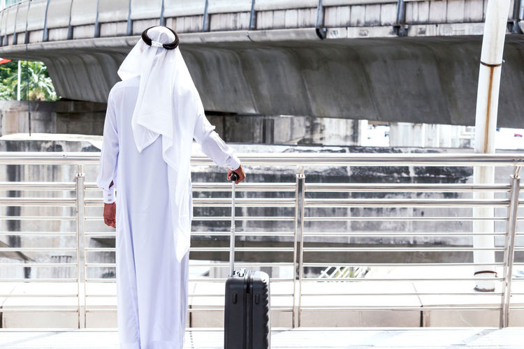 Arabic businessman with luggage walking in the city Adult Architecture Building Exterior Built Structure Clothing Day Full Length Lab Coat Lifestyles Men Occupation One Person Outdoors Railing Real People Standing Three Quarter Length Traditional Clothing Walking White Color