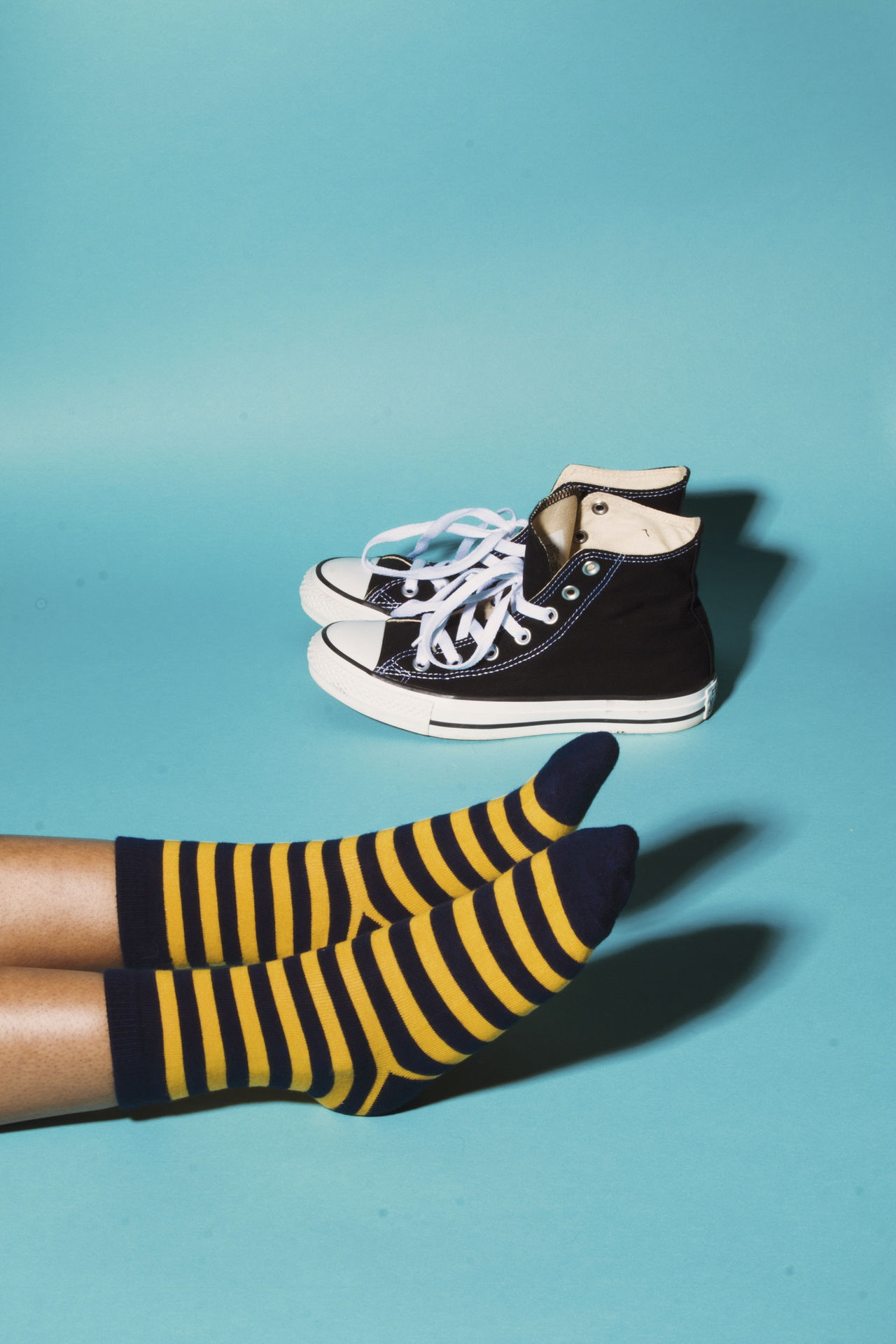 Low section of person wearing striped socks on blue background