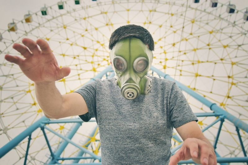 Low Angle Portrait Of Man Wearing Gas Mask Against Ferris Wheel