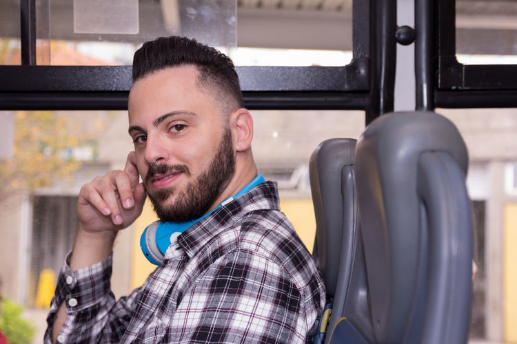 Portrait of young man sitting in bus