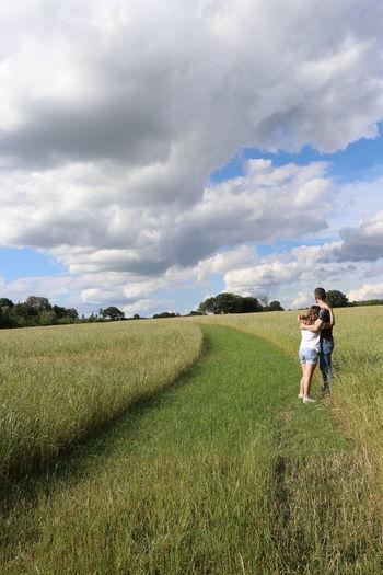 Rear view of women on field against sky