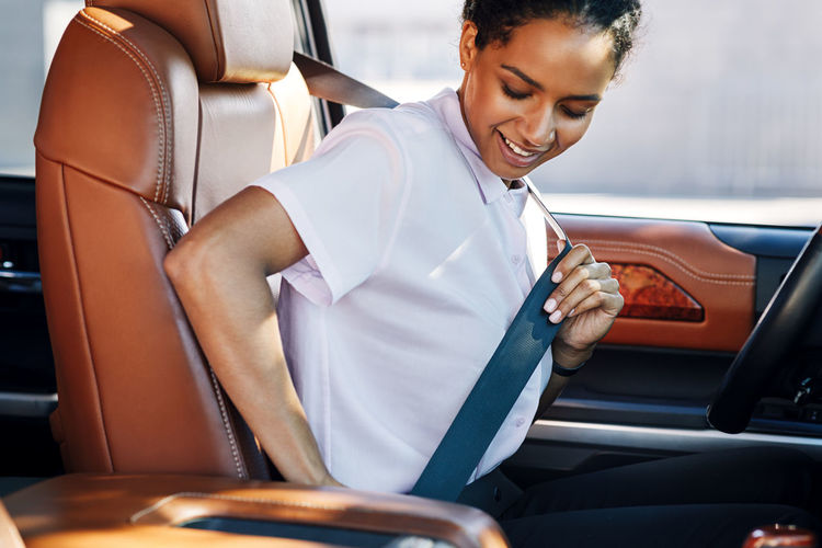 Young woman adjusting seat belt in car
