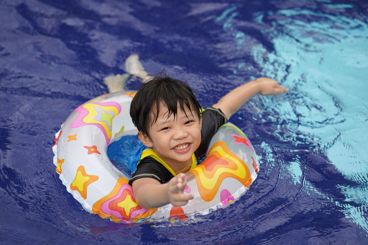 High angle portrait of cute boy with inflatable ring in swimming pool